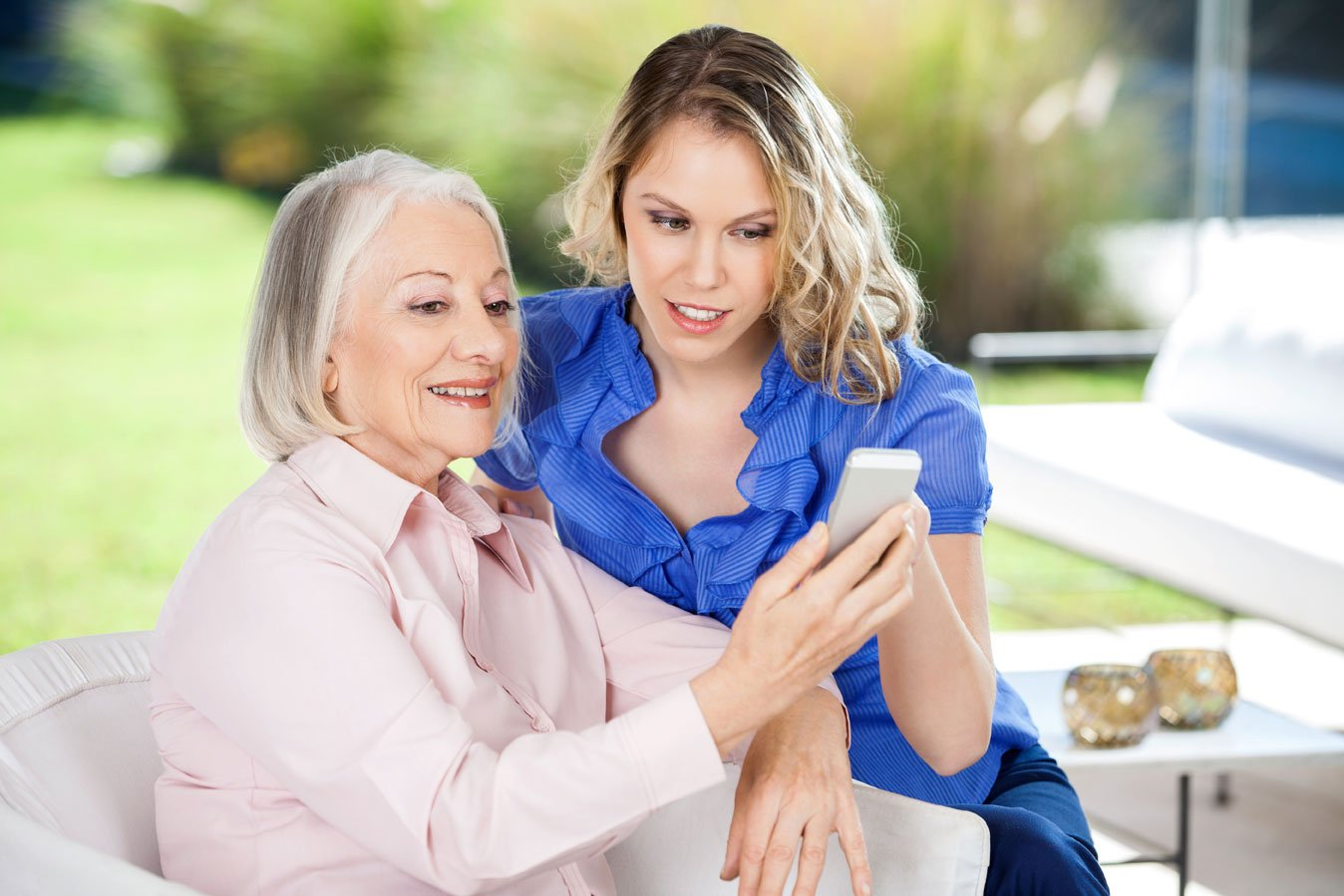 Granddaughter-assisting-senior-woman-in-using-smartphone-at-nursing-home-porch2